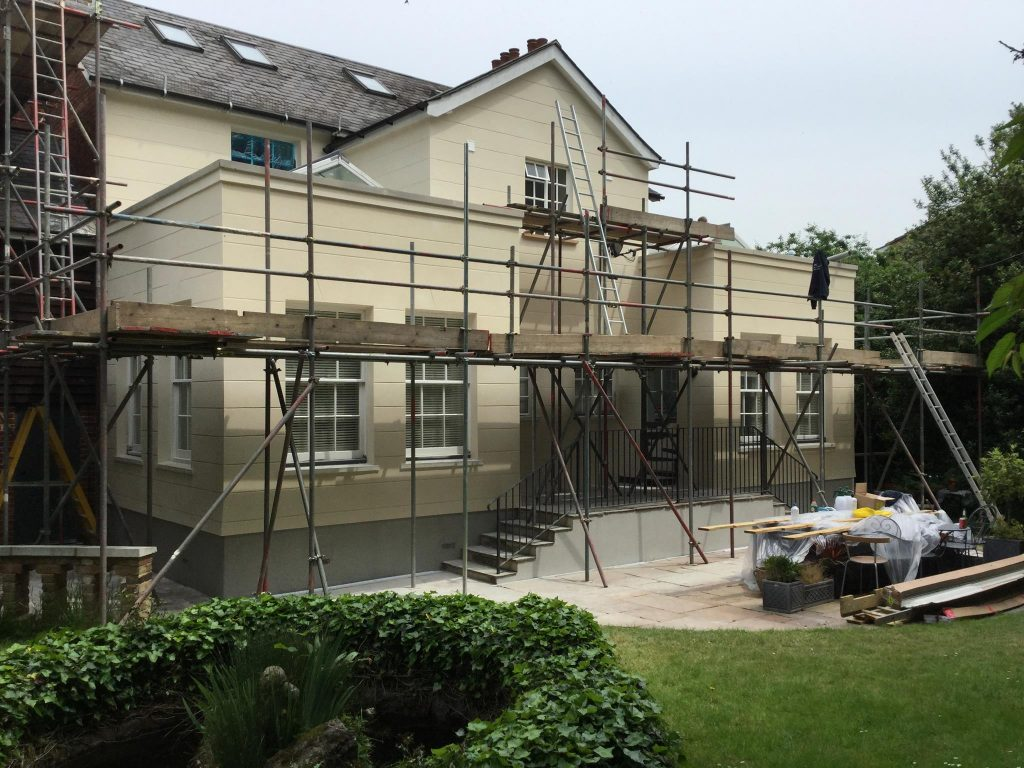 Back garden of a large house. Scaffolding surrounding the whole house.