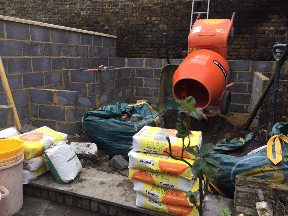 Unfinished room with exposed brickwork and cement mixer in the background