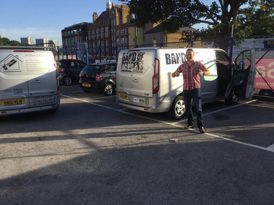 Man with is thumbs up next to two BBJ Plaster & Rendering vans