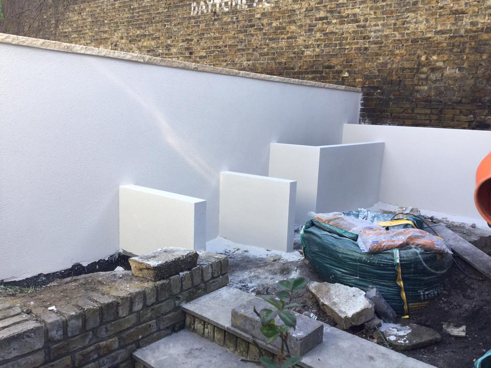 Small back garden with its walls being painted white.