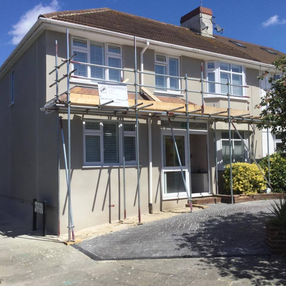 Exterior of a grey house with rendering and painting almost complete