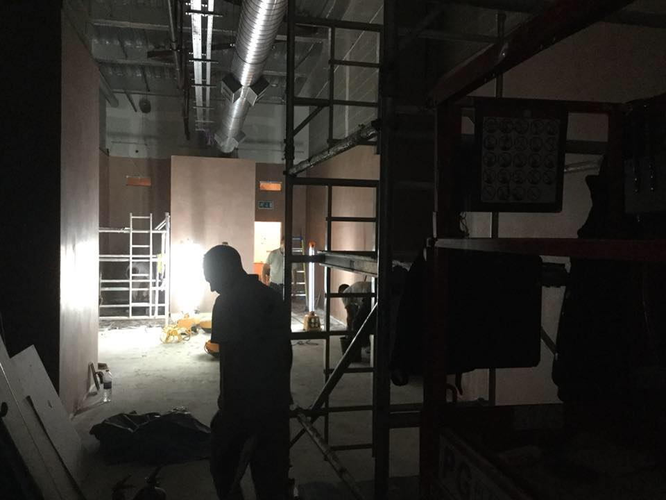 Dark interior of a commercial space with men in the background screeding the floor.