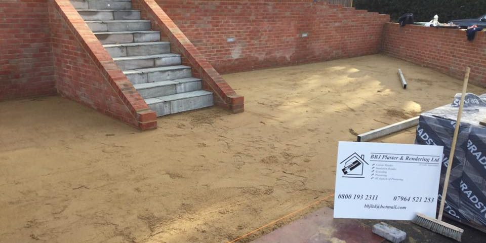 BBJ Plaster & Rendering poster next to an unfinished driveway