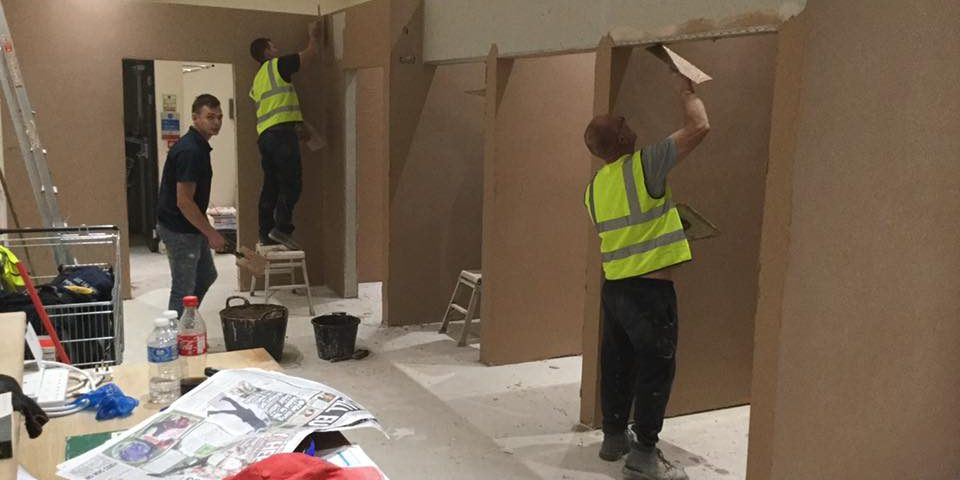 Men plastering the inside of a commercial space