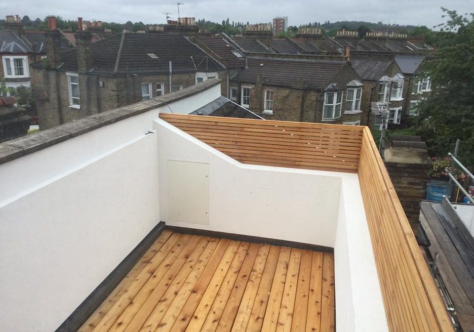 Upstairs viewing deck on a terraced house with its walls rendered and painted white. Wooden gaurd rails
